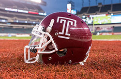 "A cherry Temple football helmet with a white Temple ""T."""