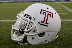 A white Temple football helmet with a cherry Temple T