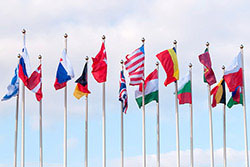 A collection of international flags flying from flagpoles