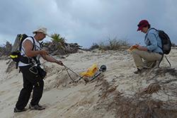 A man using a yellow georadar machine on a beach.