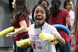 A student practicing her fencing technique with a yellow pool noodle.