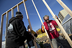 Temple volunteers spend their Global Day of Service framing a house.