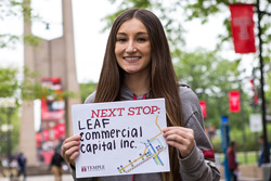 A woman with brown hair holding a sign that reads Leaf Commercial Capital, Inc.