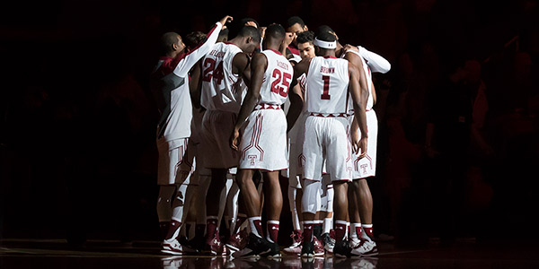 The Temple men's basketball team in a huddle on the basketball court.