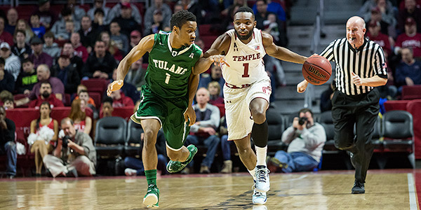 A Temple men's basketball player dribbling a ball as a Tulane player defends.