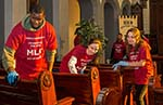 Student volunteers clean pews inside the Berean church.