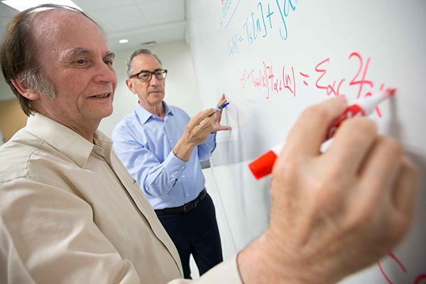 Scott Award winner John Perdew (left) works with College of Science and Technology Dean Michael Klein.