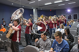 Temple marching band plays in a lecture hall during pop-up pride party.