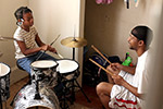 Quest Rainey teaching a young girl to play drums.
