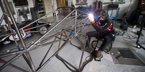 A Temple engineering student welds a portion of a race car.