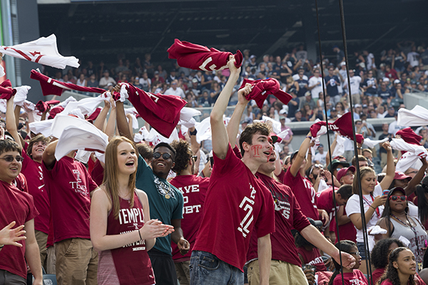 Owls fans cheer on the team in the stands, waving cherry and white flags.