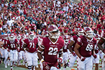Temple players take the field in front of stands filled with Cherry and White.