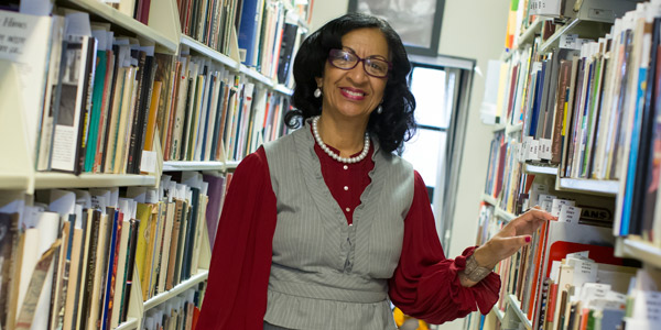 A woman in a gray suit standing near shelves of books.