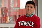 Matthew Velasquez standing in front of a window, wearing a Temple sweatshirt.